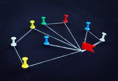 Concept of communication and delegation. Pins connected by thread. Concept of communication and delegation. Pins connected by white thread royalty free stock photo