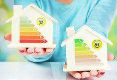 Concept comparison between normal house and low consumption house with energy efficiency rating. Closeup on concept comparison between normal house and low royalty free stock photography