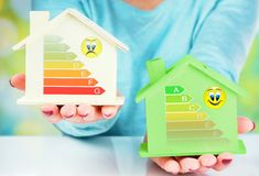 Concept comparison between normal house and low consumption house with energy efficiency rating. Closeup on concept comparison between normal house and low stock photos