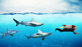 Concept of competition. Businessman escapes from sharks with a rocket Royalty Free Stock Photo