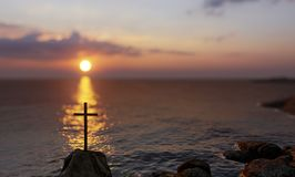 Religious christian cross standing on rock in the sea. Concept or conceptual religious christian cross standing on rock in the sea or ocean over beautiful sunset stock illustration