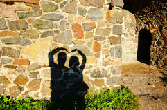 Concept or conceptual Valentine human man and woman hands silhou. Ette as heart or love symbol on stone wall Royalty Free Stock Images