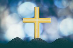 Concept conceptual yellow cross religion symbol silhouette. In nature bokeh background royalty free stock photography