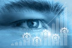 The concept is the confident vision of financial stability. A man`s eye looking straight behind a growth diagram in combination with cogwheels mechanism with stock photos