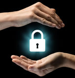Concept of confidentiality, data protection and security. Isolated image of two hands on black background. Lock icon in the center, as a symbol of Stock Photo