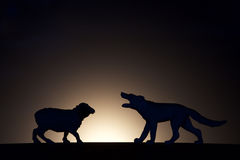 Concept conflict.Sheep versus wolf silhouette royalty free stock image