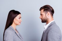 Concept of confrontation in business. Close up photo of two young serious confident people standing face-to-face to each other royalty free stock photos