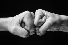 Concept of confrontation, competition etc. Image close up clash of two fists on black background. Concept of confrontation, competition etc royalty free stock images