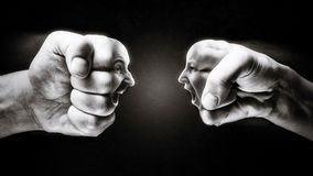 Concept of confrontation, competition, family quarrel etc. Two fists with a male and female face collide with each other on dark background. Concept of Royalty Free Stock Photos
