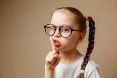 Concept of conspiracy and keeping a secret. Closeup photo of little girl wearing glasses and making a hush gesture Stock Photography