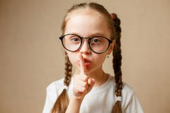 Concept of conspiracy and keeping a secret. Closeup photo of little girl wearing glasses and making a hush gesture Royalty Free Stock Images