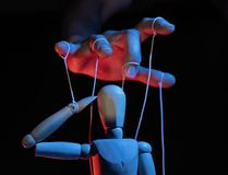 Concept of control. Marionette in human hand. Objects are colored on red and blue light stock images