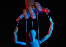 Concept of control. Marionette in human hand. Objects are colored on red and blue light royalty free stock photo