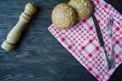 The concept of cooking. Fork, food knife, checkered napkin, buns with sunflower seeds, wooden pepper shaker. Cutlery.  stock images