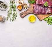 Concept of cooking two delicious raw beef steak,  cutting board, spices, and herbs, place for text, top view. Concept of cooking meat, raw ribeye steak on a Royalty Free Stock Images