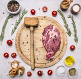 Concept cooking pork steak hammer for meat, seasoning, rosemary, parsley, oil and salt, are laid out around a wooden cutting board Royalty Free Stock Image