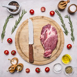 Concept cooking pork steak knife for meat, seasoning, rosemary, parsley, oil and salt, are laid out around wooden cutting board Stock Photography