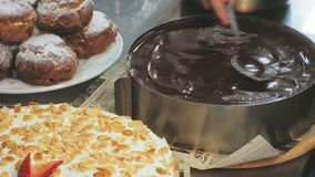 The concept of cooking. Professional pastry chef makes a delicious cake, closeup. The concept of cooking. A professional pastry chef pours a ready-made sponge stock video footage