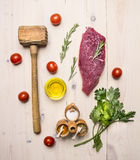 Concept cooking raw beef steak, rosemary, wooden hammer for beating the meat, oil, herbs and spices wooden rustic background to Royalty Free Stock Images