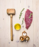 Concept cooking raw beef steak, rosemary, wooden hammer for beating the meat, oil, herbs spices on wooden rustic background to Royalty Free Stock Photos