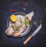 Concept cooking raw cod with herbs and lemon in a frying pan wooden rustic background top view close up Royalty Free Stock Image