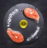 Concept cooking salmon steak on a stone cutting board with salt, pepper and oil, top view. Concept cooking salmon steak on a stone cutting board with salt Royalty Free Stock Photo