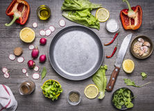 Concept cooking vegetarian food ingredients laid out around the pan with a knife spices space for text on rustic wooden backgr Stock Photo
