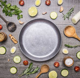 Concept cooking vegetarian food ingredients laid out around the pan with a knife spices space for text on rustic wooden backgr Stock Photos