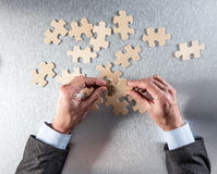 Concept of corporate strategy, cooperation, managing togetherness or oneness. Businessman hands thinking to connect jigsaw pieces for concept of corporate Stock Image
