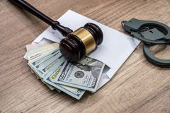 Dollars in an envelope, handcuffs and hammer judges. The concept of corruption - dollars in an envelope, handcuffs and hammer judges stock photos