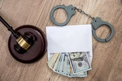 Dollars in an envelope, handcuffs and hammer judges. The concept of corruption - dollars in an envelope, handcuffs and hammer judges royalty free stock photo