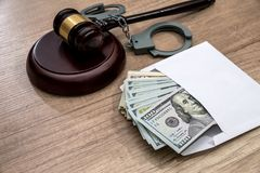 Dollars in an envelope, handcuffs and hammer judges. The concept of corruption - dollars in an envelope, handcuffs and hammer judges stock images