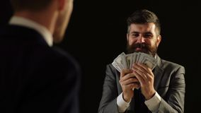 Concept of corruption. A man in a suit boasts money in front of another man. Concept of corruption. A man in a suit boasts money in front of another man stock footage