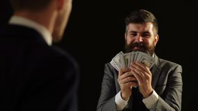 Concept of corruption. A man in a suit boasts money in front of another man.  stock video footage