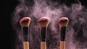 Concept of cosmetics and beauty. Make-up brushes with pink powder explosion on black background. In slow motion stock footage