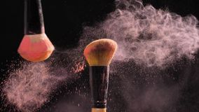 Concept of cosmetics and beauty. Make-up brushes with pink powder explosion on black background
