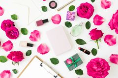 Concept with cosmetics - lipstick, eye shadows, nail polish, pink roses and clipboard and notebook on white background. Flat lay,. Top view stock photography