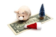 The concept of the cost of celebrating the New Year of the pig or how much it costs to celebrate NY in America. A toy pink piglet. A red Santa Claus hat, a royalty free stock image