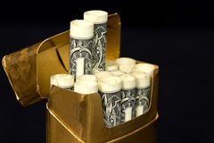 Concept - Costly Habit Cigarettes. Gold cigarette pack filled with rolled dollars symbolic of expensive habit royalty free stock images