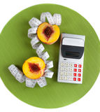 Concept of counting calories. ( peach, calculator and tape measure stock image
