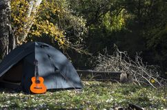 The concept of a country vacation or picnic. Guitar near the camp tent on the background of the forest and grass on sunny warm day; The concept of a country stock image