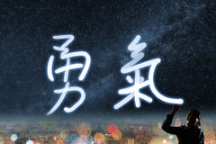 Concept of courage. Silhouette asian business woman light drawing. The chinese words means courage stock photography
