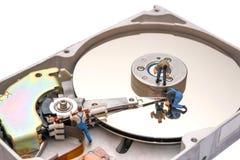 Concept créatif avec les personnes miniatures Travailleurs réparant l'unité de disque dur Images libres de droits
