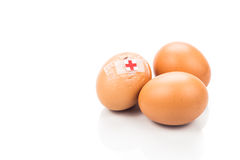 Concept of cracked egg with bandage next to two other eggs. Royalty Free Stock Images