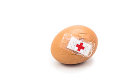 Concept of cracked egg with bandage with other eggs on tray. Stock Image