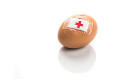 Concept of cracked egg with bandage with other eggs on tray. Royalty Free Stock Photo