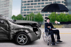 Concept of crash insurance. Portrait of disabled businessman sitting on wheelchair under an umbrella. Concept of crash insurance Royalty Free Stock Images