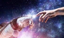 Concept of creation. Mixed media. Astronauts hands in touch as symbol for creation. Mixed media Royalty Free Stock Photos