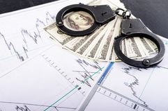 Concept of crime, bribe, detention. Handcuffs, one hundred dollar banknotes and result of polygraph lie detector test. Top. View, flat, overhead, selective stock photography