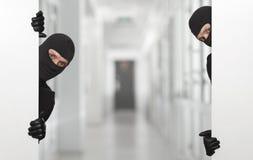 Concept criminel - voleur se cachant derrière un signe blanc vide Image stock
